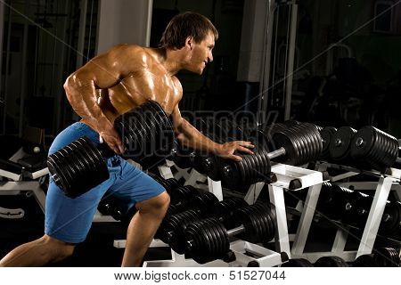 very powerful athletic guy exercises with dumbbells in the gym poster