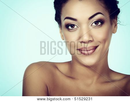 Young mulatto fresh woman with beautiful makeup looking at camera, isolated on blue, toned