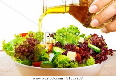 Fresh salad with olive oil isolated on white background, pouring salad dressing into cutting vegetables, organic food, healthy nutrition concept