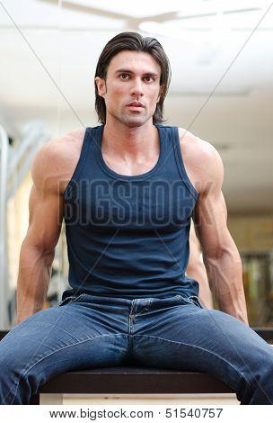 Handsome, Muscular Man Sitting On Desk Indoors