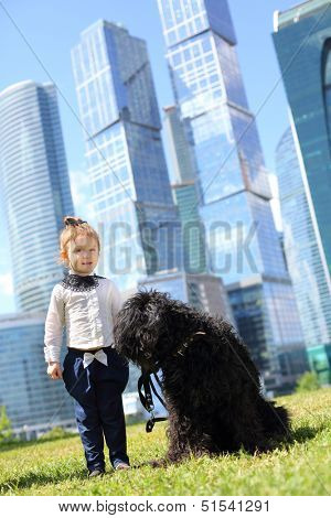 Little cute girl stands near big black dog near skys?rapers at sunny day.