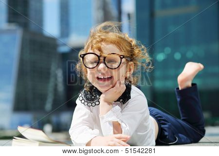 Little cute girl in glasses lies on border and smiles near skys?raper at sunny day.