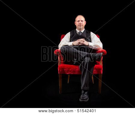 Successful Business Man In Vest And Tie Sitting In Red Velvet Chair On Black Background