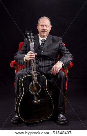 Musician In Business Suit Sitting In Red Velvet Chair Holding Guitar