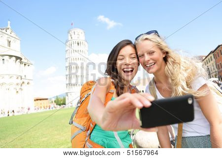 Travel tourists friends laughing taking photo with smartphone. Women girlfriends traveling in Europe smiling joyful having fun taking self-portrait picture in Pisa by Leaning Tower of Pisa, Italy. poster