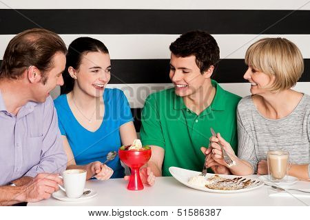 Happy Family Of Four In Restaurant