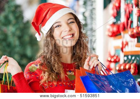 Portrait of happy woman in Santa hat carrying shopping bags at store