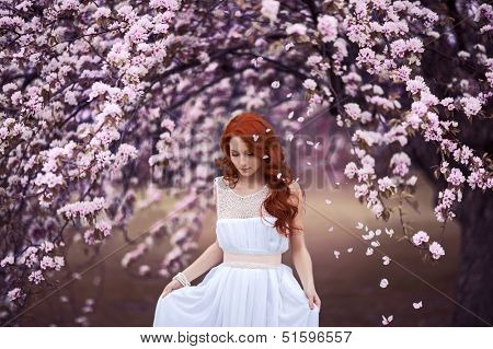 Beautiful young girl under the flowering pink apple-tree