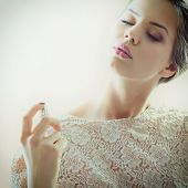 Girl with perfume, young beautiful woman holding bottle of perfume and smelling aroma, toned soft beige and noise added poster