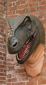 A Wall Mounted Model of a Prehistoric Dinosaur. poster
