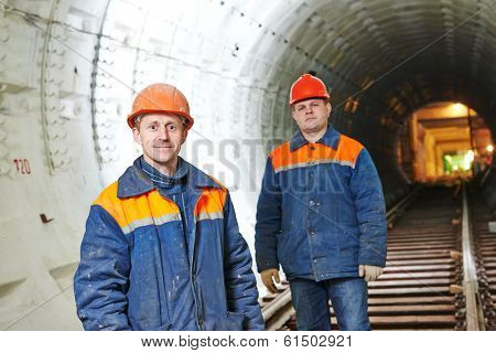 Two tunnel workers mounters at underground subway metro construction site