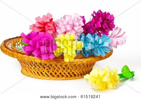 Many colored paper flowers in the basket and one flower near the basket