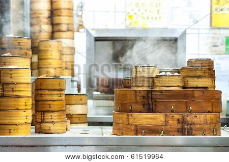 TAI PO HUI MARKET, HONG KONG - NOV 17, 2013 - Stacked dim sum steamers at a Hong Kong restaurant. Dim sum is popular throughout Hong Kong and Cantonese-speaking communities. The food is usually steamed and brought to the tables in bamboo steamers. poster