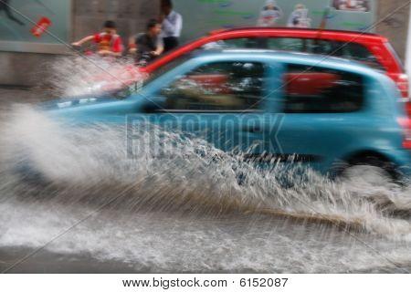 Car Driving On Flooded Street Causing A Huge Splash.