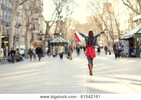 Barcelona, La Rambla shopping woman. Female shopper walking happy away with shopping bags raised up. From the famous landmark street in Catalonia, Spain.