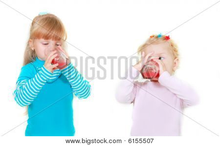 Two Girls Drinking Juice Over White