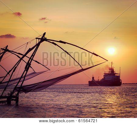 Vintage retro hipster style travel image of Kochi chinese fishnets on sunset and modern ship. Fort Kochin, Kochi, Kerala, India