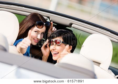 Two happy girls sitting in the car and thumbing up look back and have fun while having little car trip