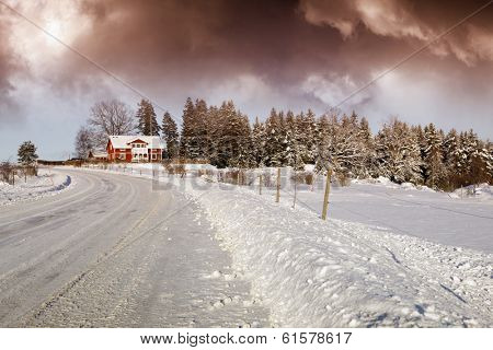 old cottages, houses draped in a winter snow-scape, dark red snow clouds above, scenery from sweden