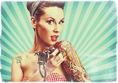 Photo of beautiful pin-up girl with tattoos and tattoo machine tattooing herself and looking at the camera. Retro styled imagery, toned image, grungy, noise added. poster