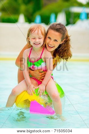 Portrait Of Happy Mother And Baby Girl Sitting On Ball In Swimming Pool