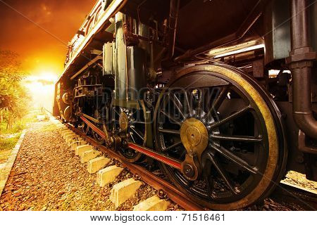 Iron Wheels Of Stream Engine Locomotive Train On Railways Track Perspective To Golden Light Forward