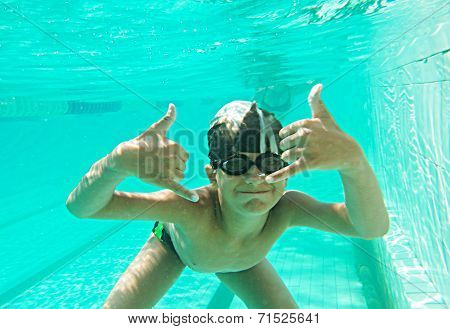 Portrait of a cute little boy swimming underwater gesturing and a lot of copyspace