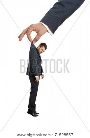big hand holding small discontented businessman. isolated on white background