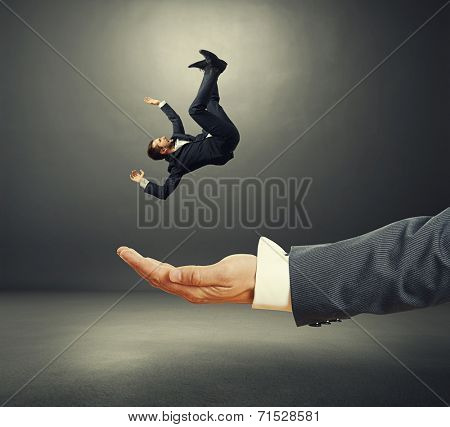 big palm catching small startled businessman in dark room