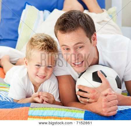 Attentive Father And His Son Watching A Football Match