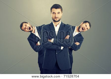 two screaming men behind confident businessman over dark background