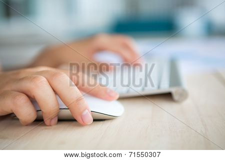 Closeup of business woman hand typing on keyboard and mouse