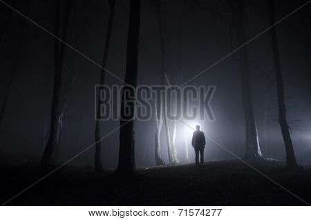 Man in dark forest with fog at night