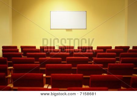 empty conference hall with screen. rows of a chairs.