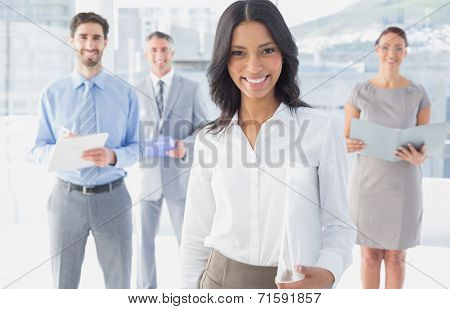 Business woman holding a folder in front of fellow workers