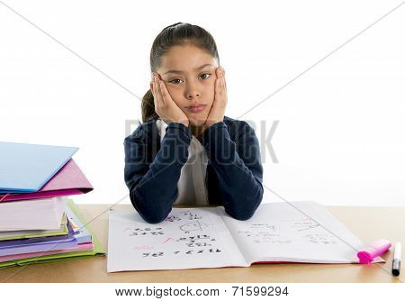 sweet little female hispanic child schoolgirl studying on desk looking bored and under stress with a tired face expression in children education and back to school concept isolated on white background poster