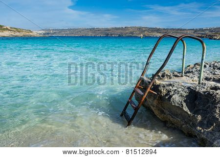 Ladder leading down into a beautiful blue sea