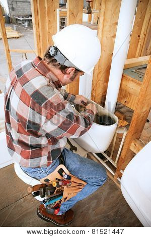 Plumber installing a toilet on a construction site.