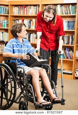 Two disabled kids in the school library, one in a wheelchair and one with crutches.