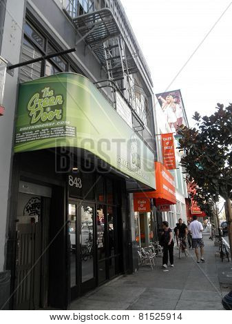 People Move Along The Sidewalk In Front Fo The Green Door, Medical Marijuana Pot Shop Store In Soma