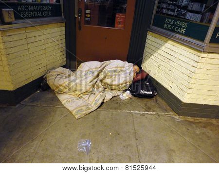 Bundled Up Homeless Person Sleep In Door Way Of Store Under A Blanket With Head On Pillow Late At Ni