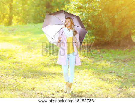 Petty Sensual Woman With Umbrella In Sunny Autumn Day