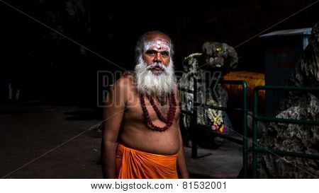 KUALA LUMPUR, MALAYSIA - JANUARY 31, 2015: A priest at the Sri Mahamarriamman temple takes a walk inside the cave temple. Hundreds of thousands of devotees gather here for the Thaipusam prayers.