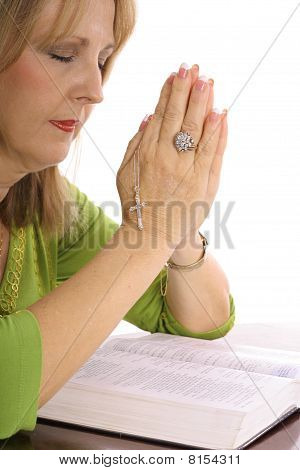 woman praying over the bible with rhinestone cross