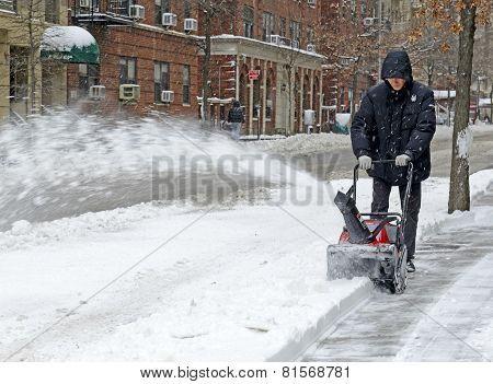 Person with snowblower clearing street, Manhattan, New York