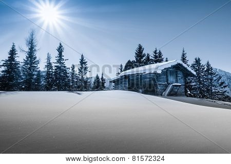 Mountain sun over the ski hut in blue