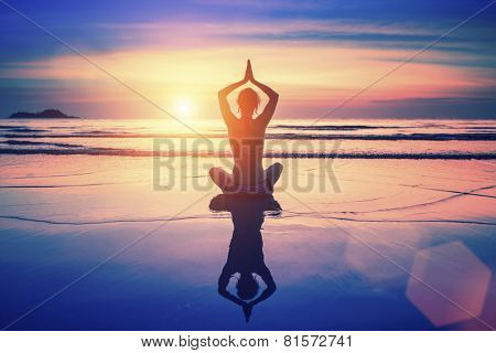 Yoga woman sitting in lotus pose on the beach with reflection in water during sunset.