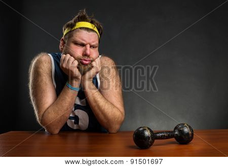 Sad man with a dumbbell