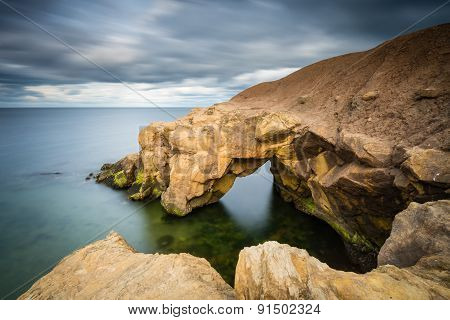 Saddle Rocks at Cullercoats Whitley Bay here at high tide using a long exposure to blur the water and clouds poster