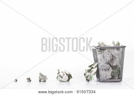 isolated wastebasket full of waste paper